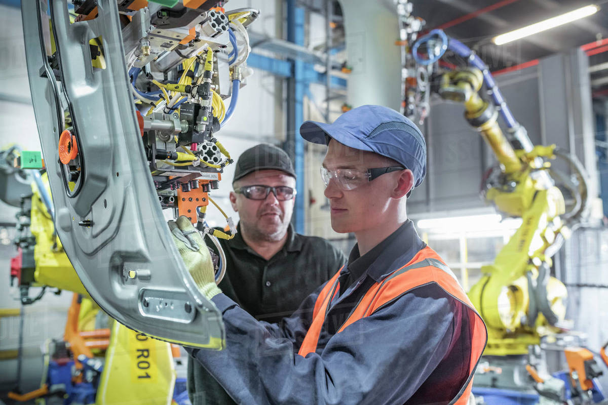 Apprentice engineer with mentor and robots in car factory Royalty-free stock photo