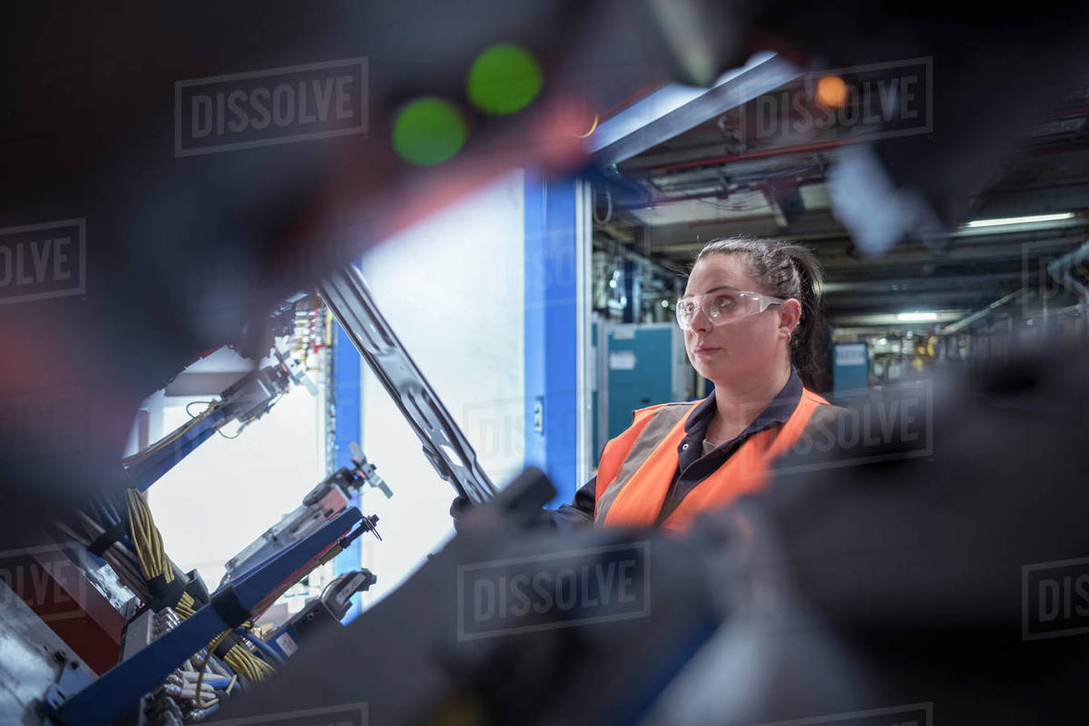 Female worker assembling vehicle roofs in car factory Royalty-free stock photo