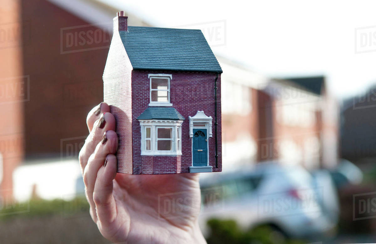 Teenage girl holding man made model of house in front of housing estate, shallow focus, close up of hand Royalty-free stock photo