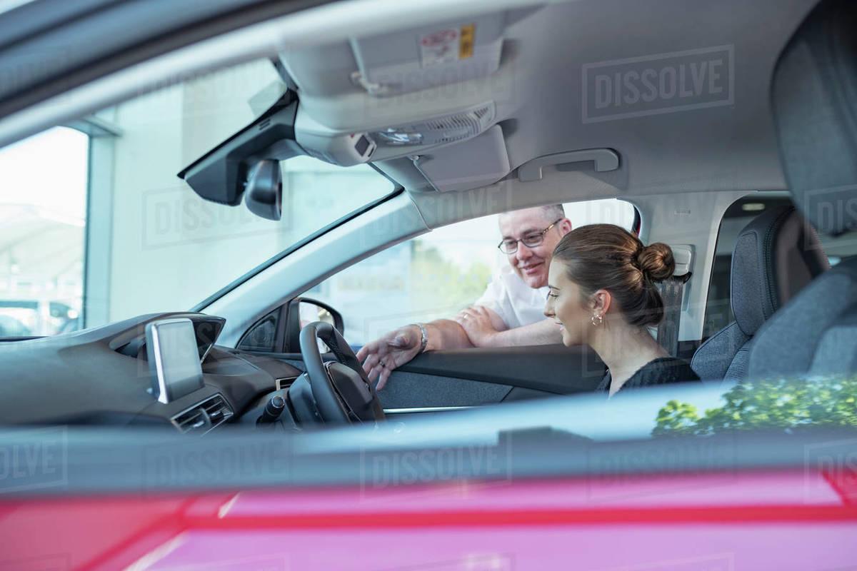 Salesman demonstrating car controls to customer in car dealership Royalty-free stock photo