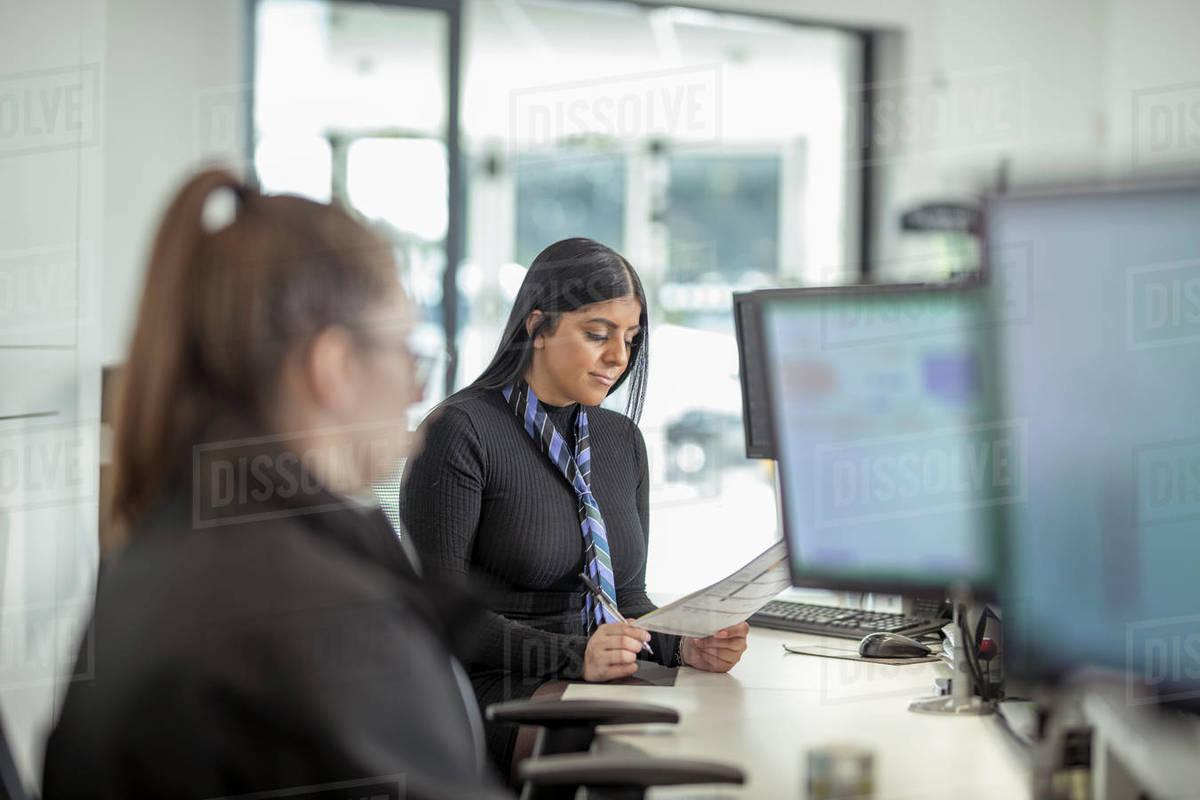 Female apprentice service advisors in car dealership Royalty-free stock photo