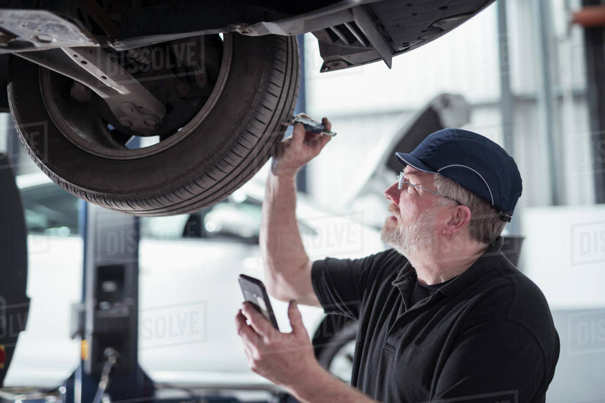 Engineer checking car tyre during service in car service centre Royalty-free stock photo