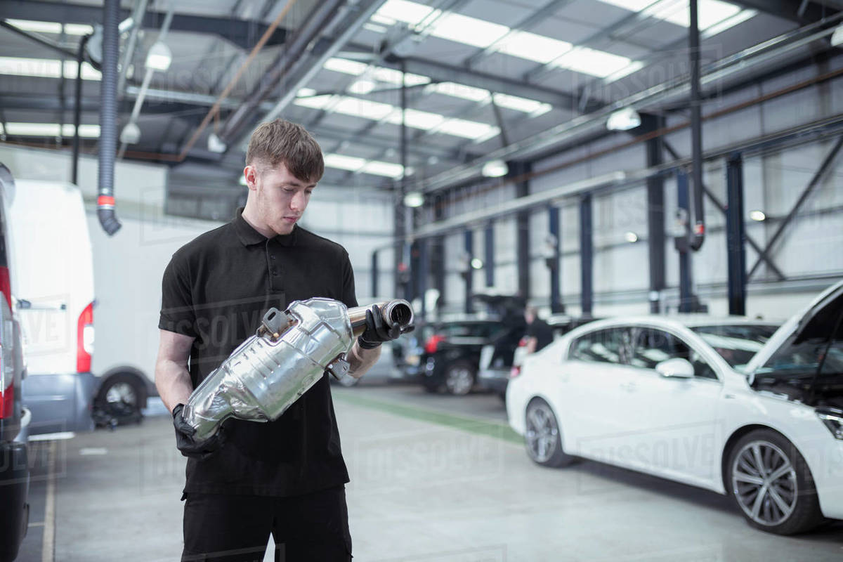 Apprentice holding catalytic converter in car service centre Royalty-free stock photo