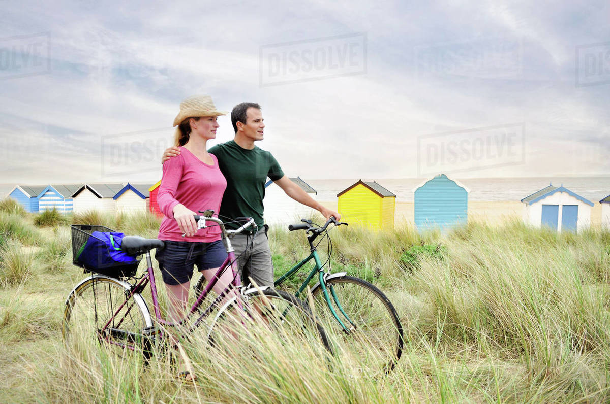 Mid adult couple with bicycles at coast, Southwold, Suffolk, UK Royalty-free stock photo