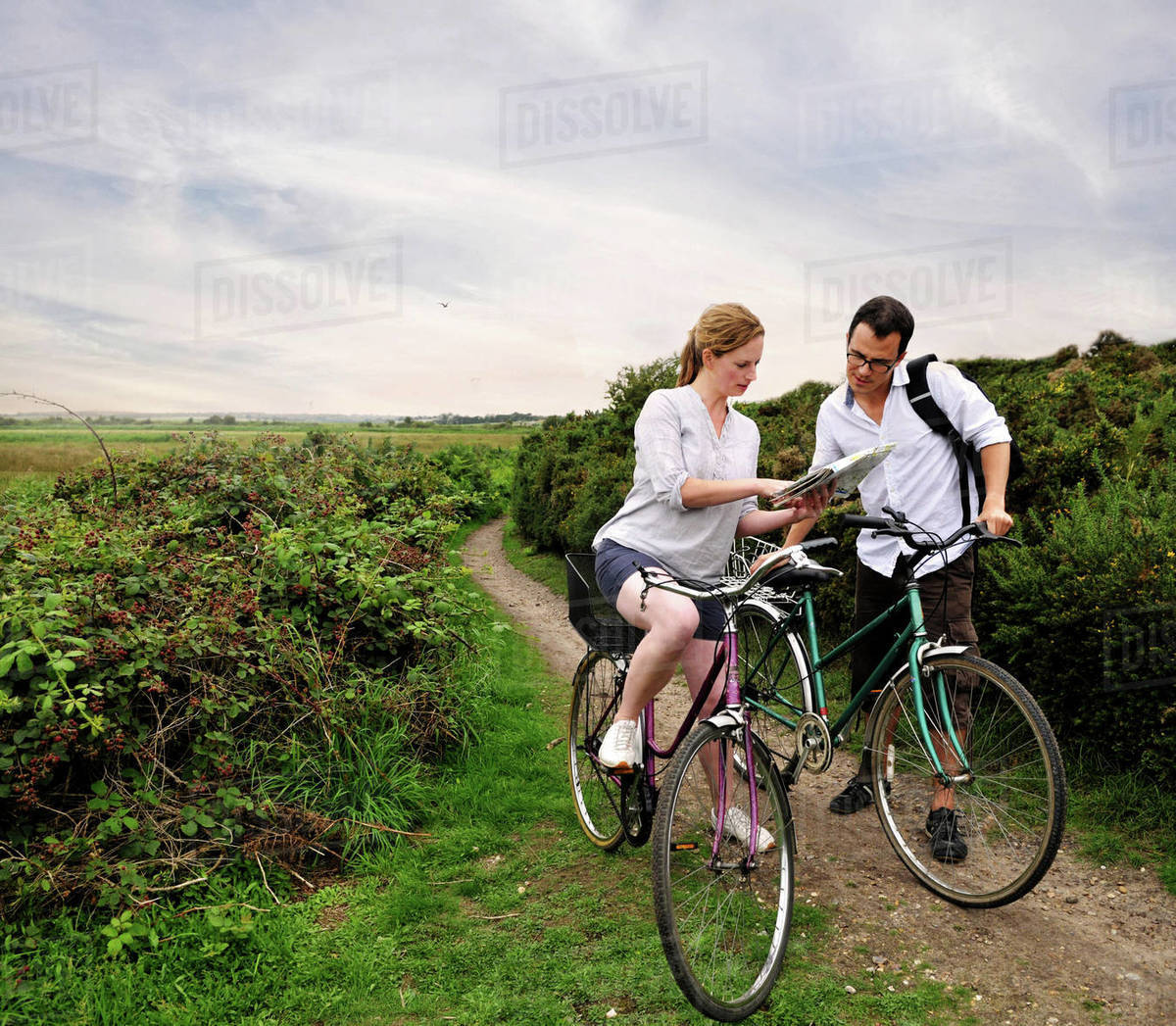 Mid adult cycling couple on rural dirt track looking at map, Southwold, Suffolk, UK Royalty-free stock photo