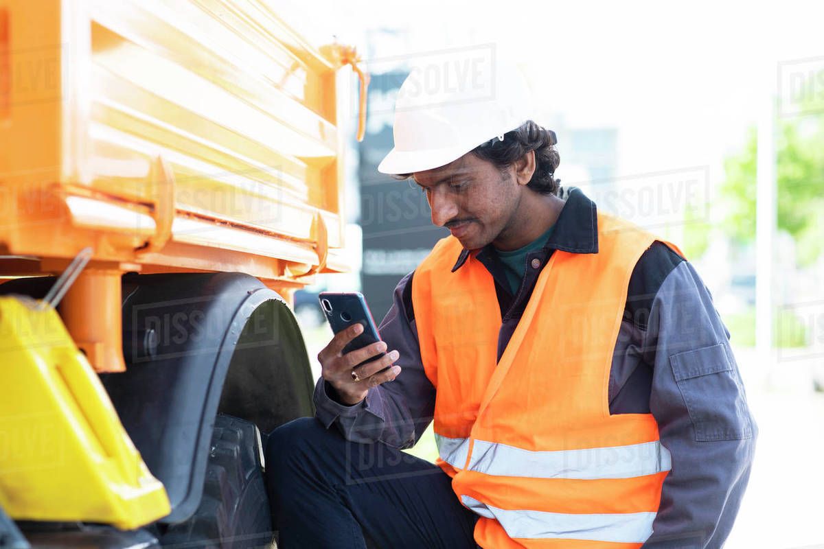 Male engineer standing next to yellow truck looking at smartphone Royalty-free stock photo