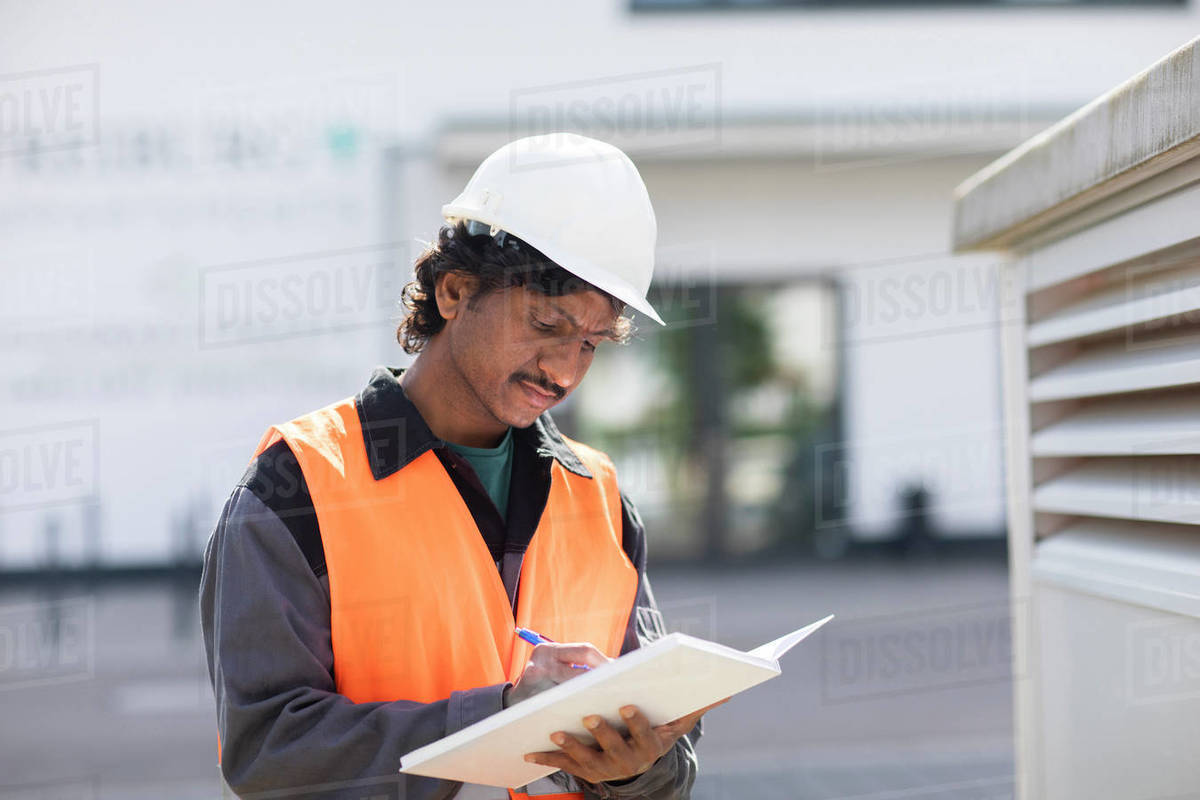 Male engineer outside industrial building writing in notebook Royalty-free stock photo