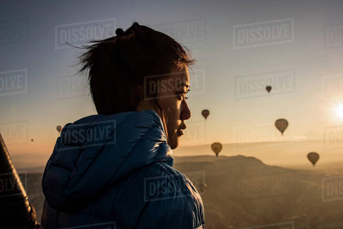Woman enjoying view, hot air balloons flying in background, Göreme, Cappadocia, Nevsehir, Turkey  Royalty-free stock photo