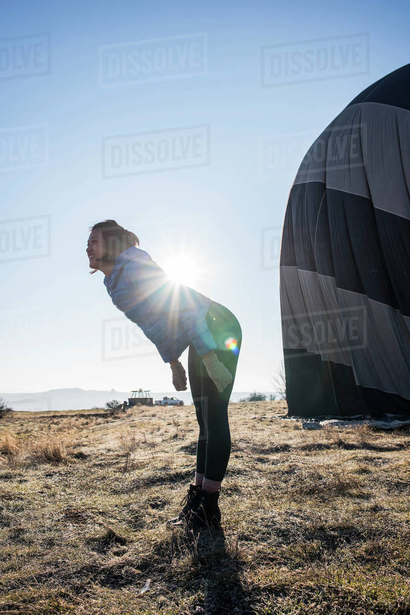 Woman bending forward against sunlight, hot air balloon in background, Göreme, Cappadocia, Nevsehir, Turkey Royalty-free stock photo