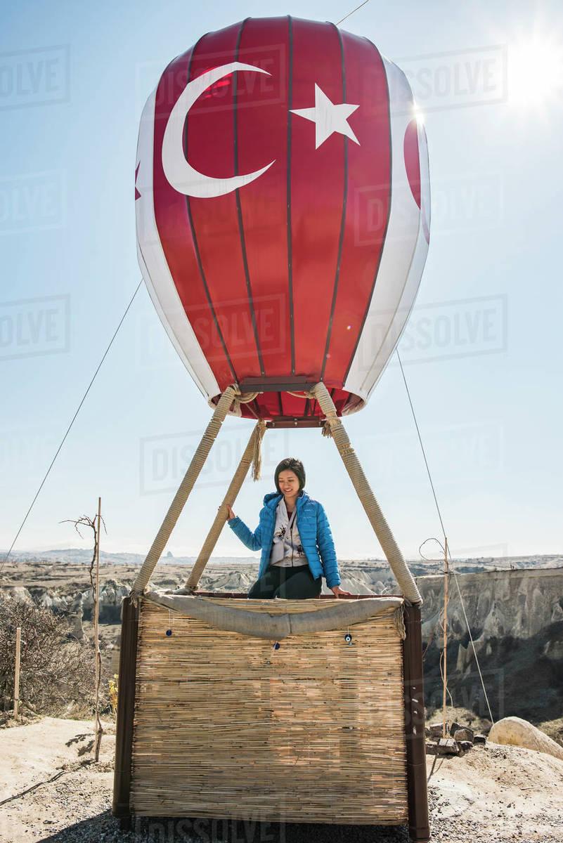 Woman sitting on basket of hot air balloon overlooking fairy chimney valley, Göreme, Cappadocia, Nevsehir, Turkey Royalty-free stock photo