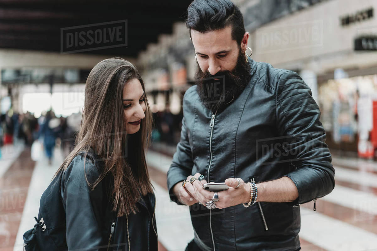 Couple using smartphone in station Royalty-free stock photo