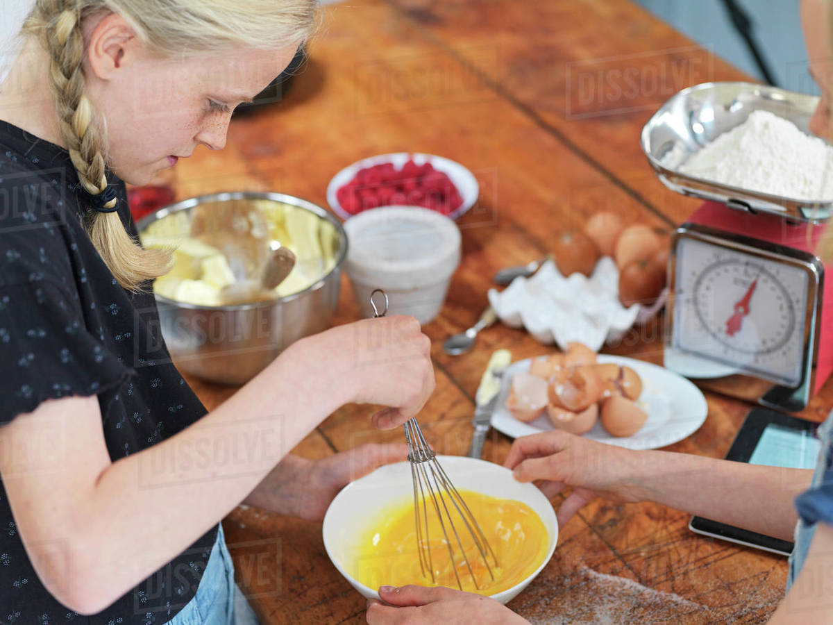 Girl and her sister baking a cake, whisking eggs in a bowl at kitchen table Royalty-free stock photo
