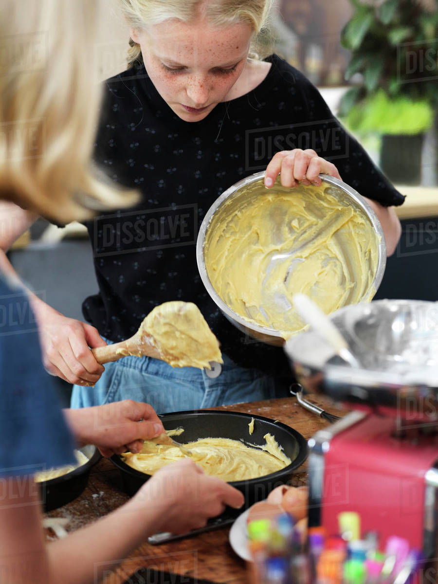 Girl and her sister baking a cake, pouring cake mixture into cake tin at kitchen table Royalty-free stock photo