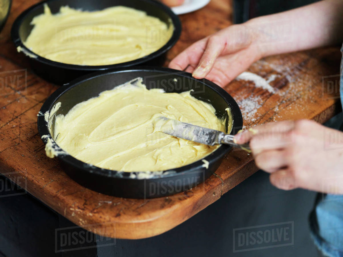 Girl baking a cake, smoothing cake mixture in cake tin at kitchen table, cropped close up of hands Royalty-free stock photo