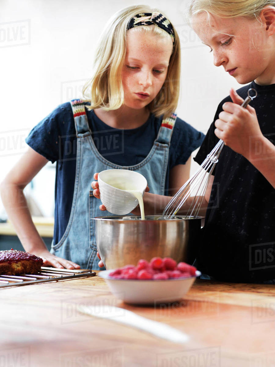 Girl and her sister baking a cake, pouring cream into mixing bowl at kitchen table Royalty-free stock photo