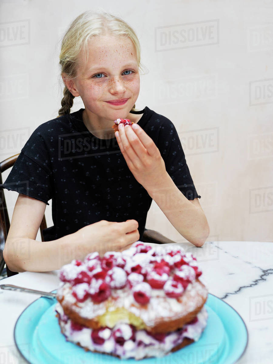 Girl eating her homemade cake with fresh raspberries at kitchen table, portrait Royalty-free stock photo