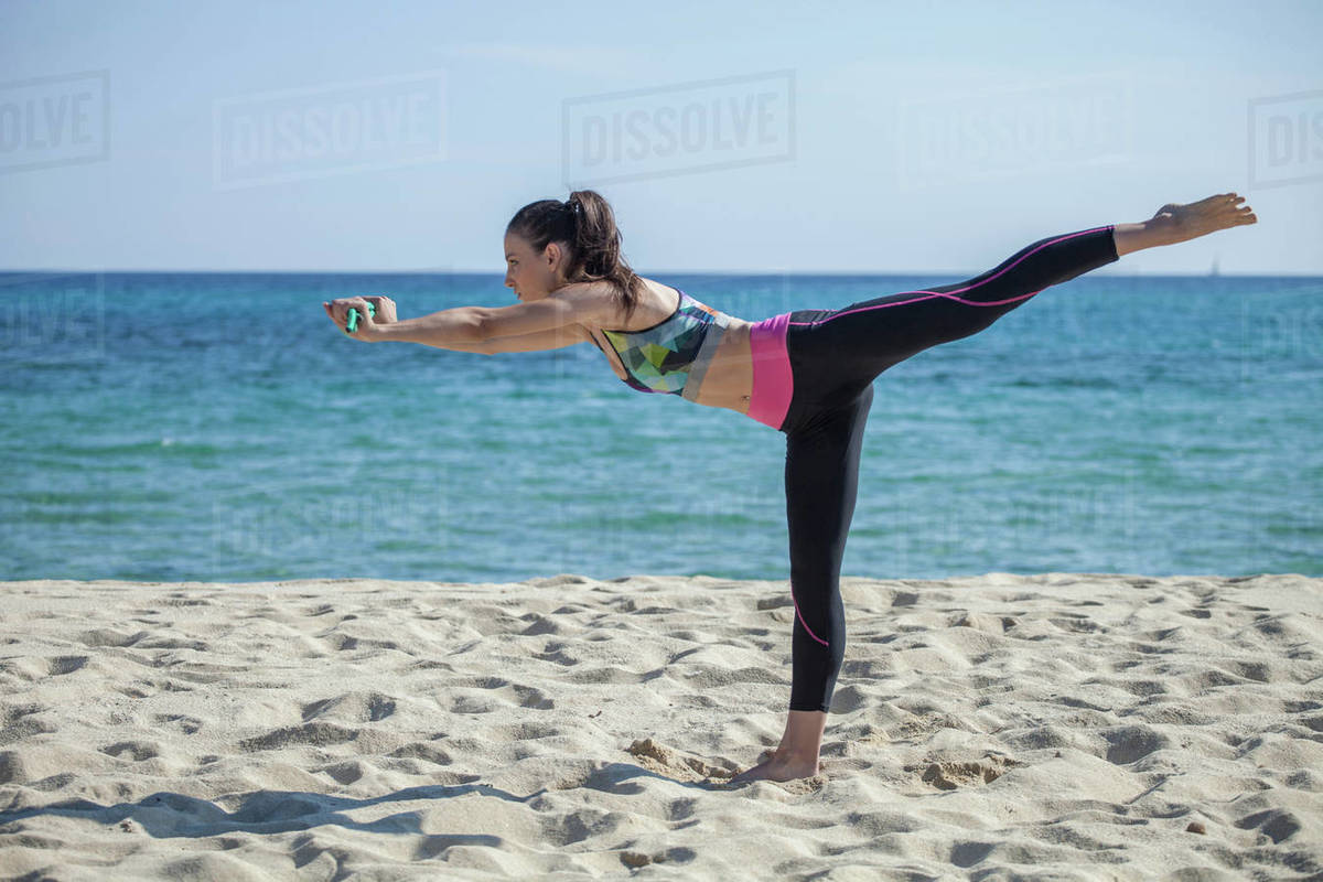 Side view of woman standing on a sandy beach, doing yoga. Royalty-free stock photo