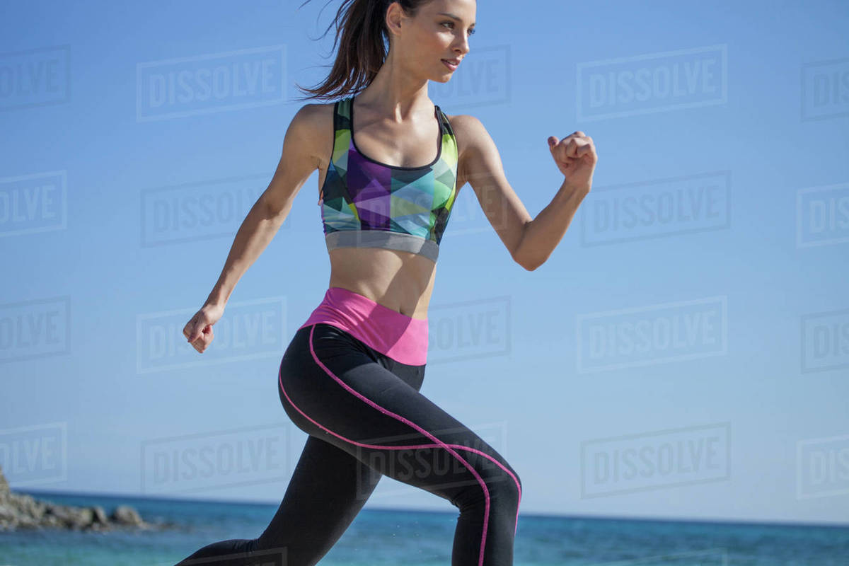 Close up of young woman jogging on a beach. Royalty-free stock photo