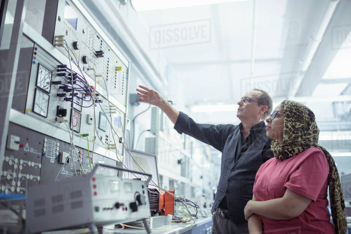 Male and female electrical engineers inspecting electrical test rig in research facility. Royalty-free stock photo
