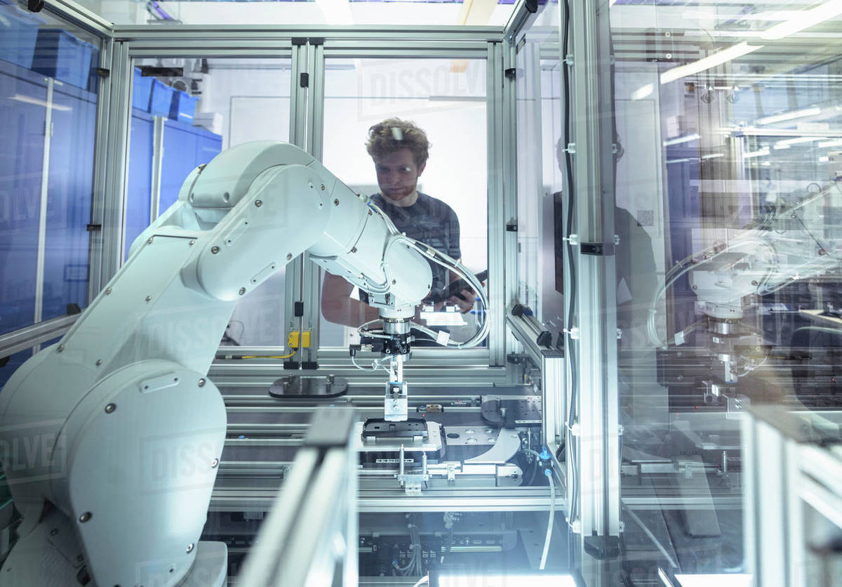 Male trainee engineer with robotic equipment in research facility. Royalty-free stock photo