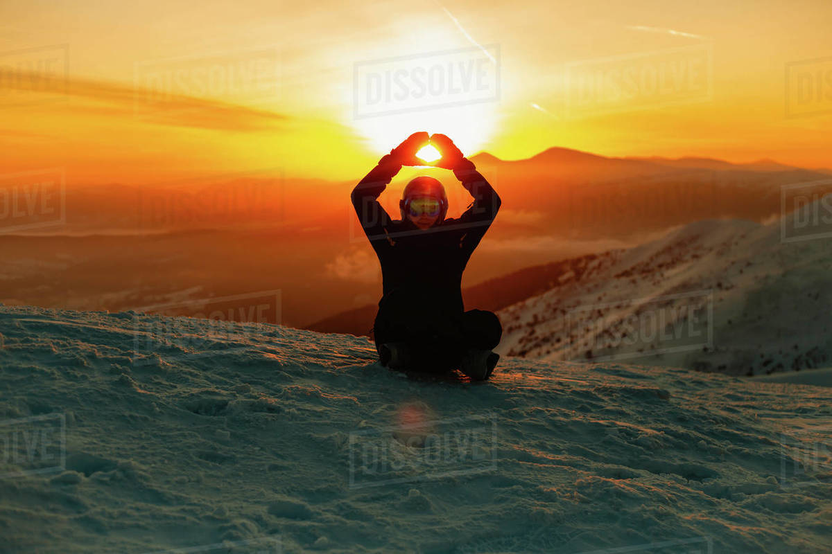 A person sitting on a snow slope, silhouetted against the sunset with arms raised above their head. Royalty-free stock photo