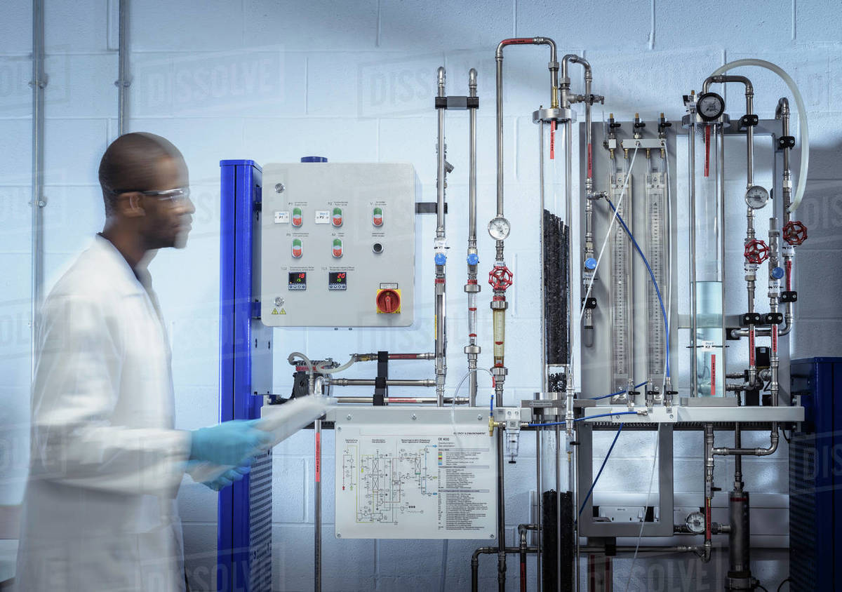 A man wearing a lab coat walking past a bank of scientific equipment. Royalty-free stock photo