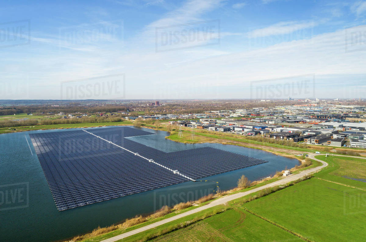 Aerial view of solar panels set on a lake in the countryside near an Industrial area. Royalty-free stock photo