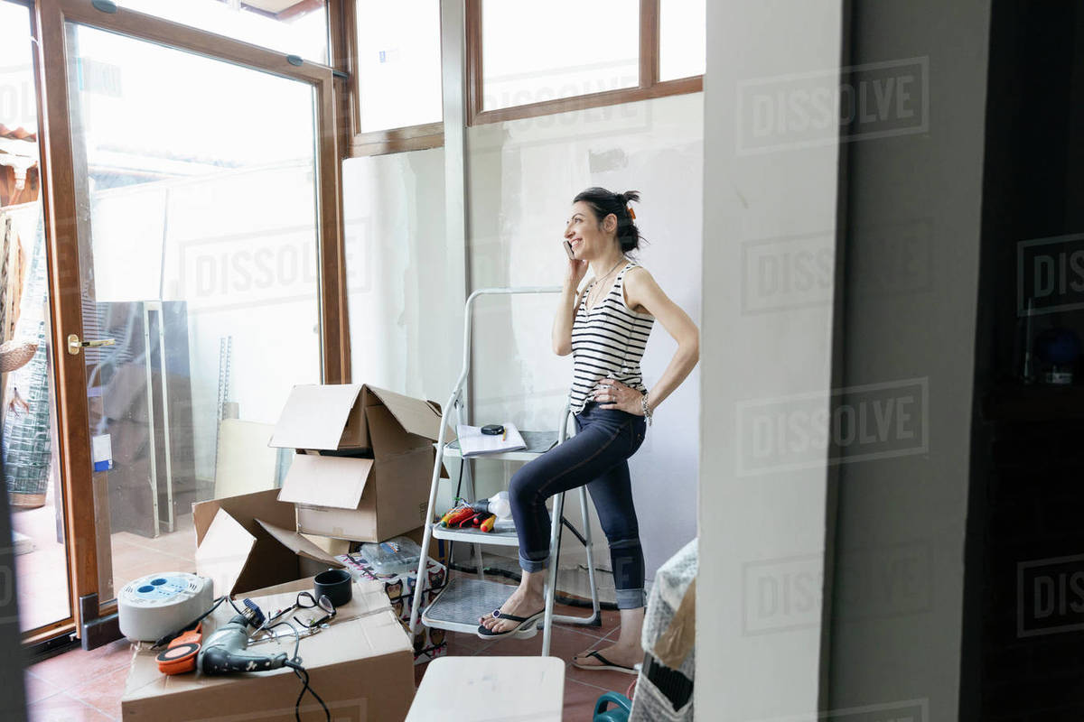 Woman standing with one foot on the bottom of a stepladder talking on a phone with cardboard boxes nearby. Royalty-free stock photo
