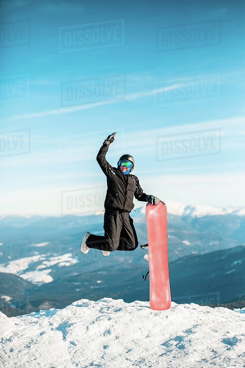 A person wearing a black ski suit, helmet and goggles jumping for joy on top of a mountain on a red snowboard. Royalty-free stock photo