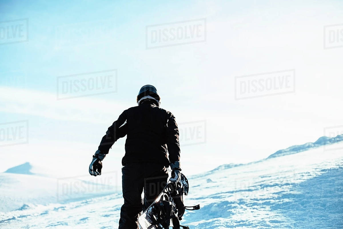 A person wearing a black ski suit and helmet holding a snowboard standing on top of a snowy mountain. Royalty-free stock photo