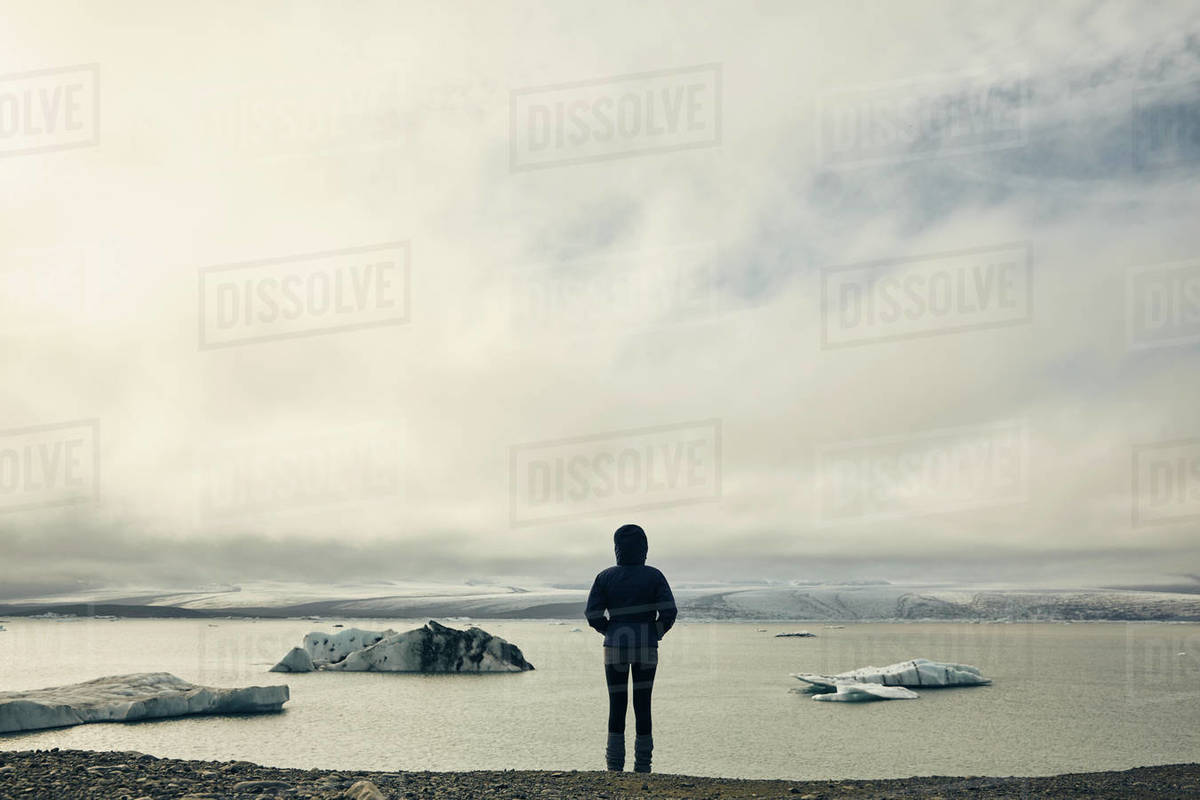 A woman on a stony beach looking out to sea and ice floes. Royalty-free stock photo