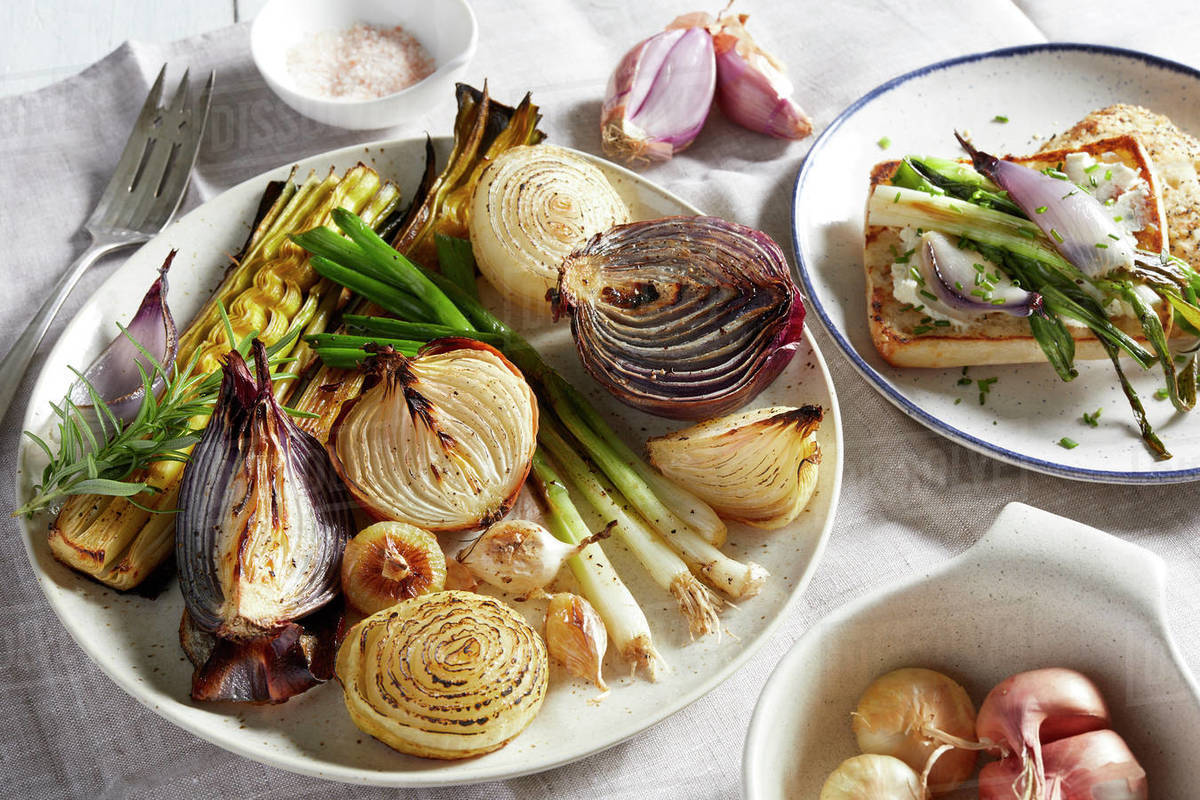 Plates and dishes with a variety of roasted onions, a selection of onions on toast and uncooked shallots in a bowl. Royalty-free stock photo