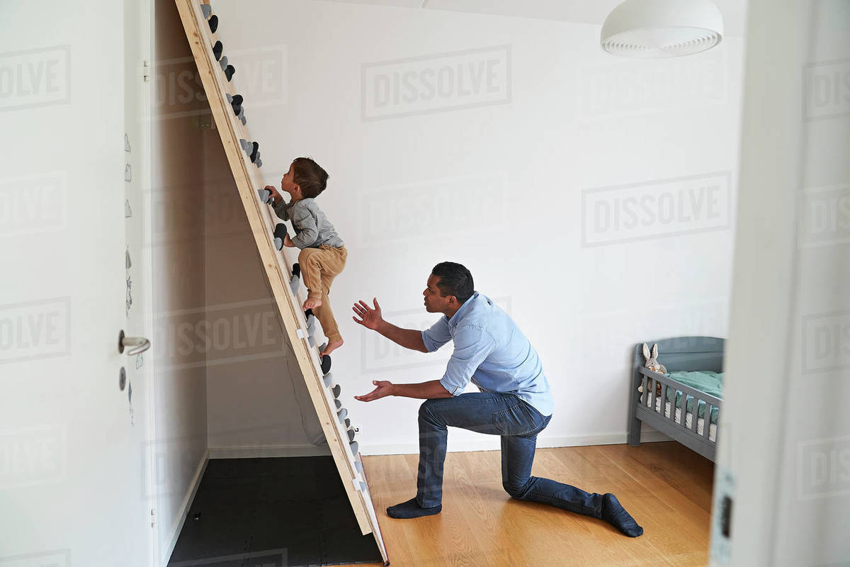A father kneeling at the bottom of a climbing wall while his son climbs up it. Royalty-free stock photo