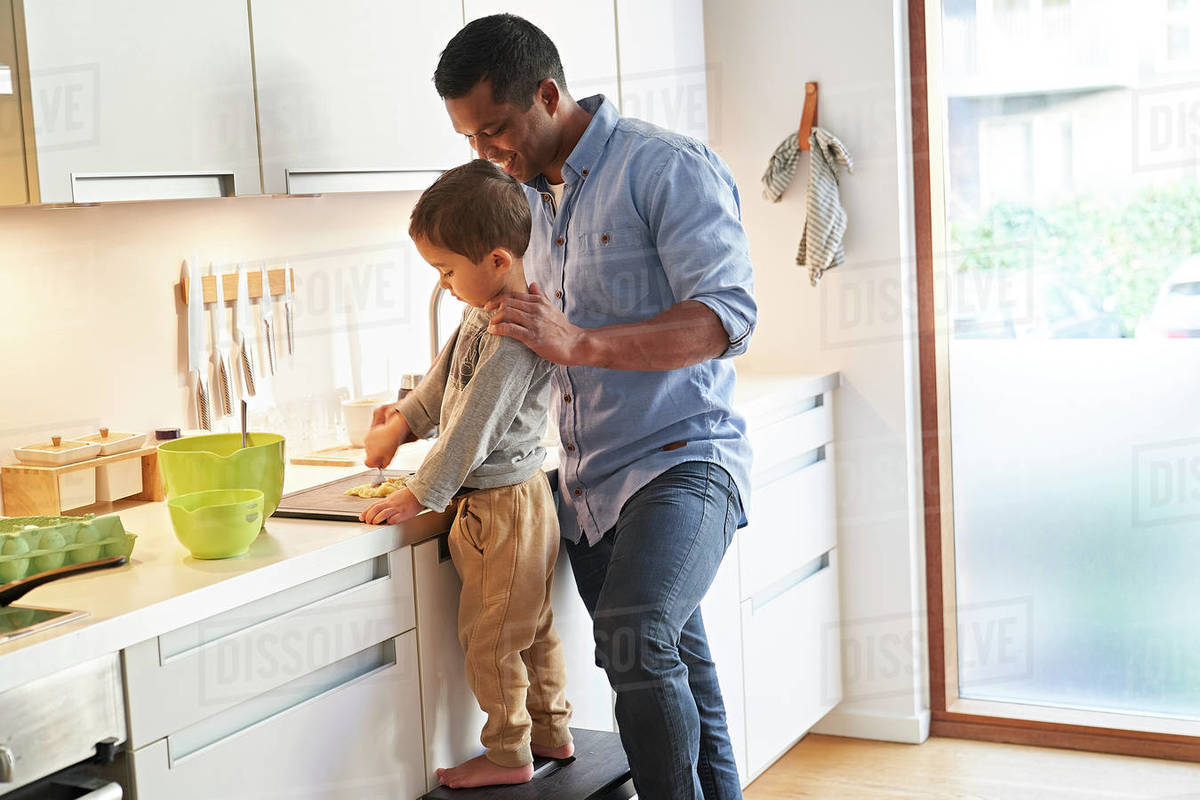 A father and son both standing at a kitchen worktop preparing food on a chopping board. Royalty-free stock photo