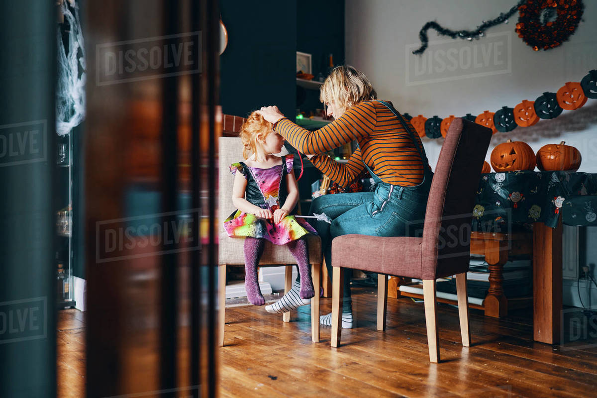 A woman painting a girls face for Halloween. Royalty-free stock photo