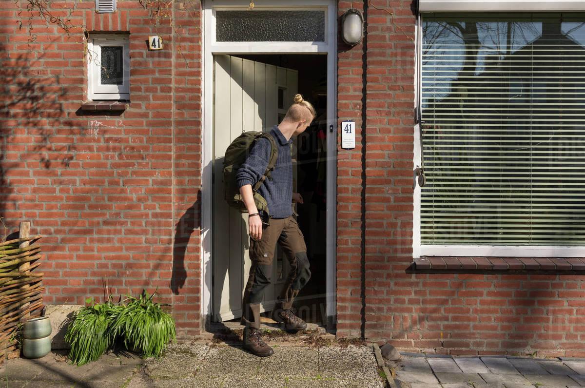 Teenage boy during Corona virus crisis, leaving house carrying a big backpack. Royalty-free stock photo