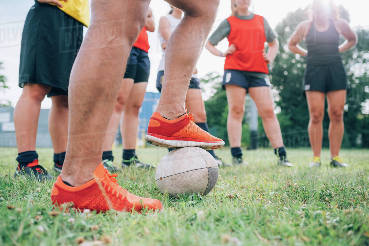 The legs and feet of a group of women standing on a training pitch one with a foot on a rugby ball. Royalty-free stock photo