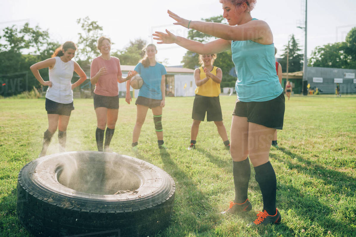 Six women at rugby training one having just thrown a tyre. Royalty-free stock photo