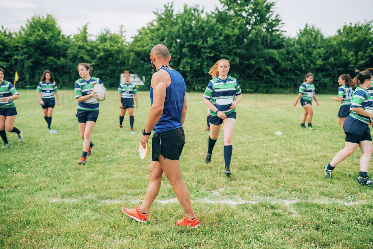 Group of women wearing blue, white and green rugby shirts on a training pitch, one running with a rugby ball with the coach watching. Royalty-free stock photo