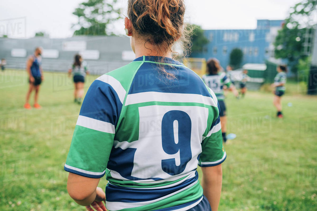 Rear view of a woman wearing a blue, green and white rugby shirt on a pitch at training with other players in the background. Royalty-free stock photo