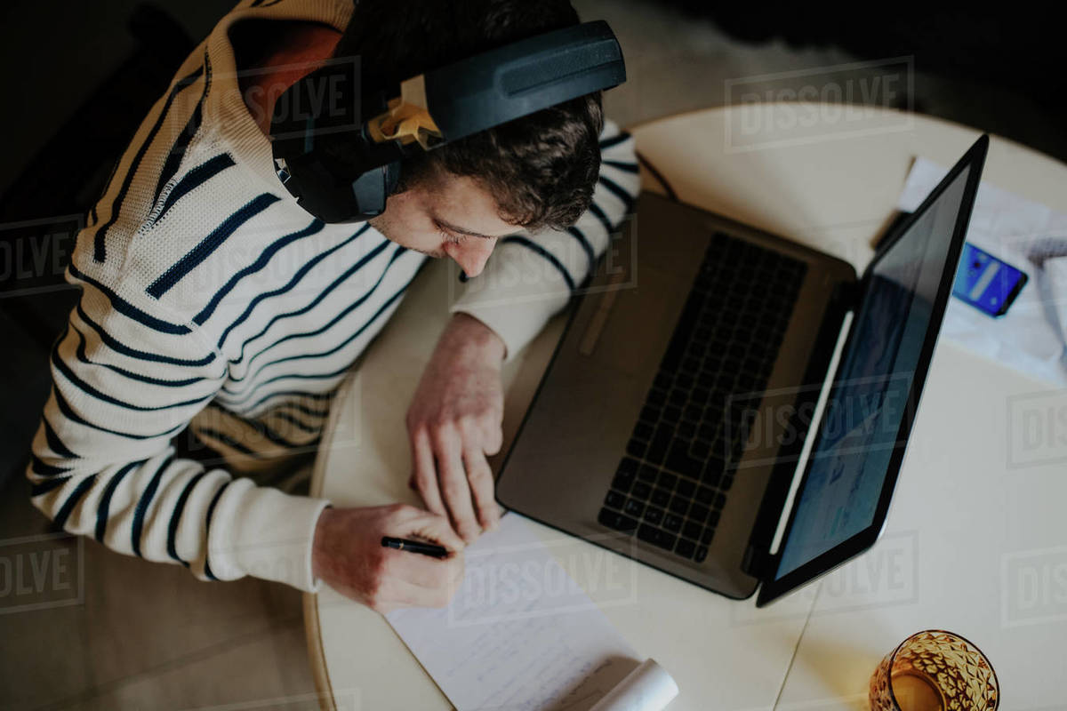 Man working at home during lockdown, using headphones and laptop, and pen and paper. Royalty-free stock photo