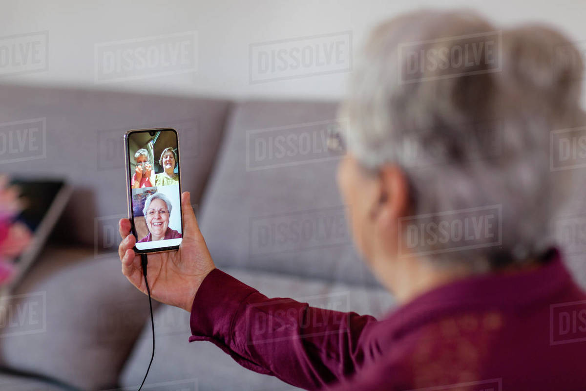 A woman holding up a mobile phone and looking at three friends on screen during social isolation, skype or whatsapp party.  Royalty-free stock photo