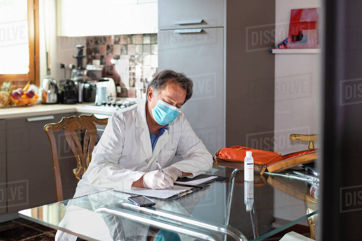 Doctor wearing a white coat, facemask and protective gloves sitting at a kitchen table writing up medical notes.  Royalty-free stock photo