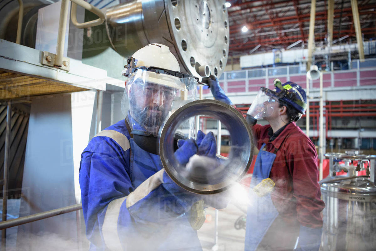 Engineers fitting parts in a  power station with liquid nitrogen. Royalty-free stock photo