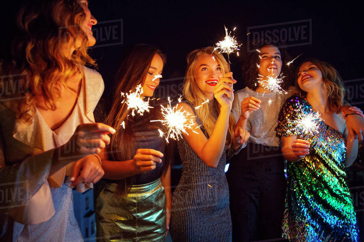 Five women dressed to go out for the evening outside with sparklers. Royalty-free stock photo