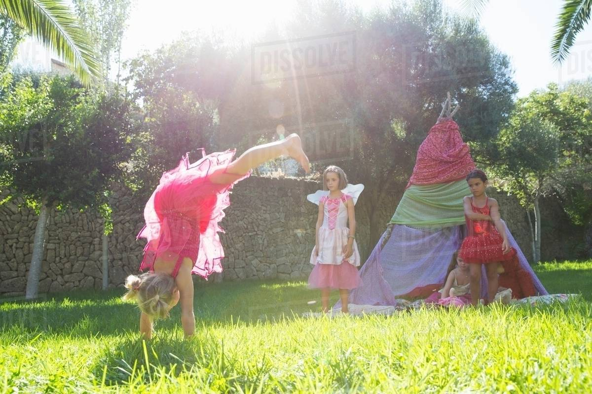 Girls watching friend in fairy costume doing handstand in garden Royalty-free stock photo