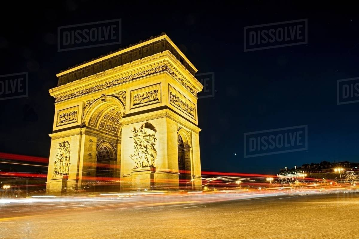 view of the arc de triomphe and traffic at night paris france