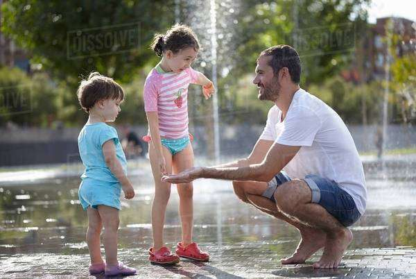 Mid adult man and two daughters playing in water fountains, Madrid, Spain Royalty-free stock photo