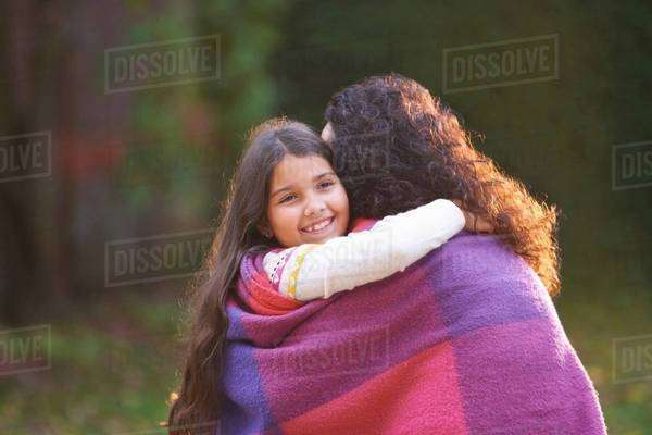 Mother and daughter wrapped in blanket in garden Royalty-free stock photo