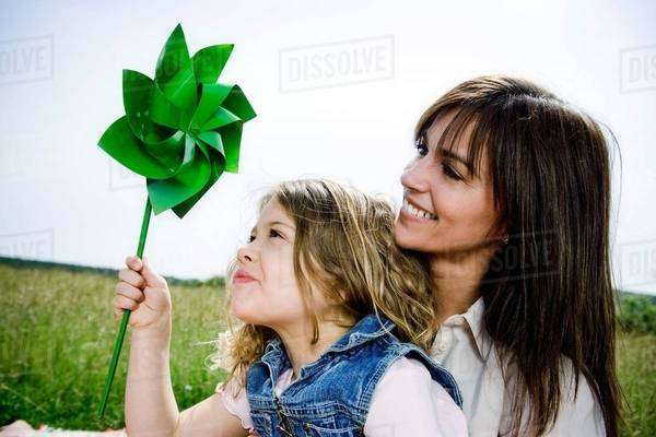 Woman and girl with toy windmill Royalty-free stock photo